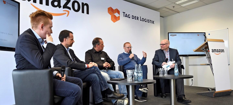 """Auf einem Podium, im Hintergrund ist an der Wand """"Amazon"""" und """"Tag der Logistik"""" zu lesen, sitzen fünf Männer mittleren Alters und diskutieren"""