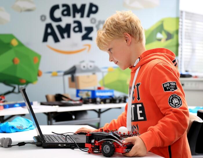 Ein blonder Junge im orangenen Hoodie blickt auf einen Laptop, neben ihm ein Fischetechnik-Transportfahrzeug