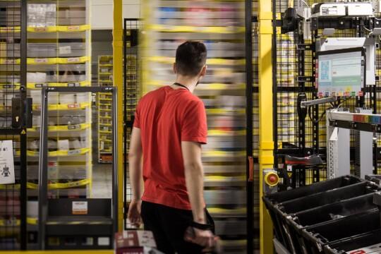 Un dipendente Amazon ripreso di spalle al centro dell'immagine osserva gli scaffali mobili del magazzino.