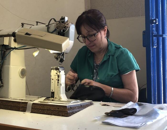 Mujer de mediana edad trabajando con una máquina de coser zaoatis, Viste una bata de color azul y en la mano tiene unas tijeras.