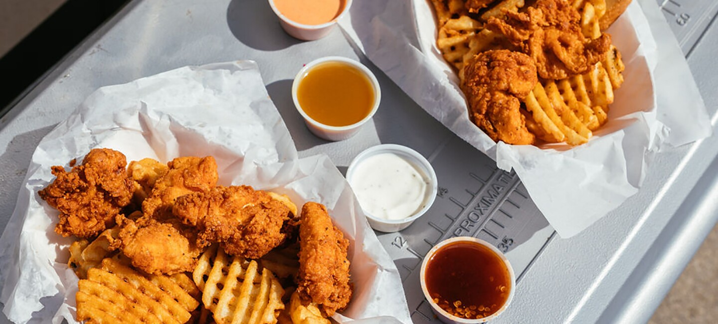 A basket of waffle fries, Texas toast, and chicken tenders, on ledge of a food truck window. To the right are four dipping sauces, and another basket of food.