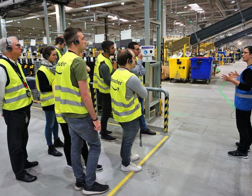 Eine Besuchergruppe in einer Logistikhalle blickt auf einen Tourguide