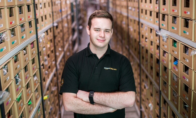 Amazon apprentice Jonathon Williams standing between shelves