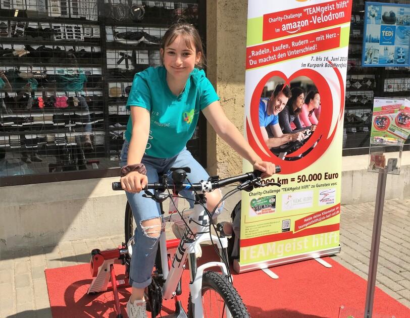 Eine junge Frau sitzt auf einem Trimmrad. Im Hintergrund steht ein Roll Up, das auf die Charity Challenge und Amazon weist.