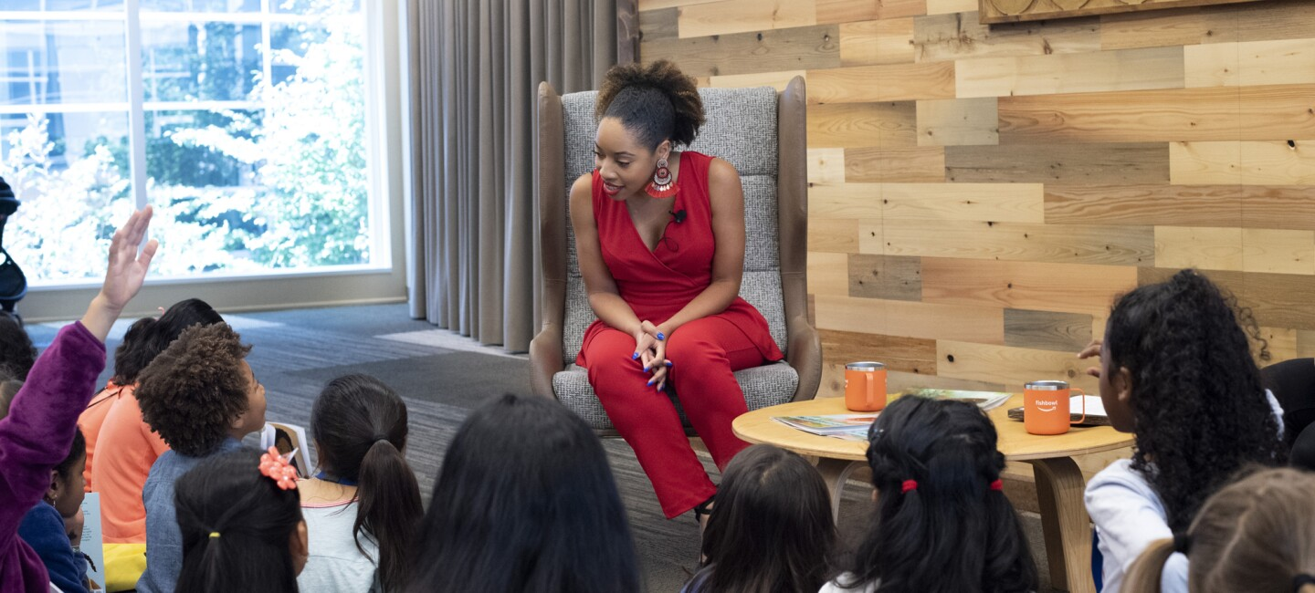 A woman sitting in a chair interacts with a group of children.