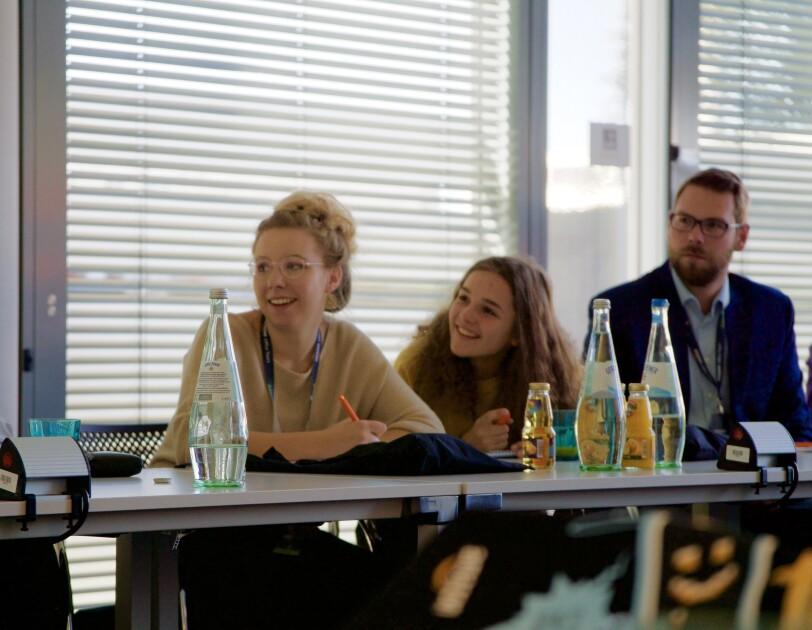 Links im Bild: die Teilnehmerinnen von Jugend gründet. Rechts ist ein Herr im blauen Anzug zu sehen. Alles sitzen an einem Konferenztisch. Im Vordergrund sind Getränke auf dem Konferenztisch.