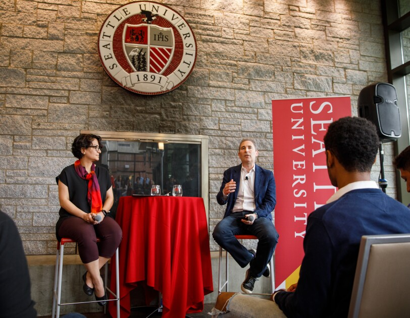 A woman, Roshanak Roshandel sits on a raised chair, next to a man, Andy Jassey, as they lead a fireside chat at Seattle University.