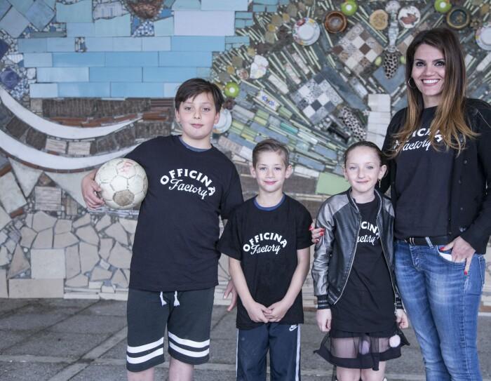 Alexandra Corona insieme a tre bambini sorridenti davanti a un murales della Biblioteca di Scampia
