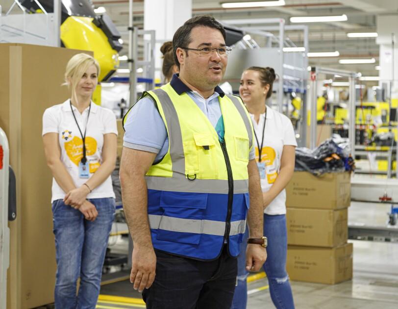 """Ein Mann mit Brille, Sicherheitsweste und dunkelbraunen Haaren in einer Logistikhalle. Im Hintergrund sieht man 2 Mitarbeiterinnen von Amazon in """"Amazon gemeinsam""""-Shirts."""