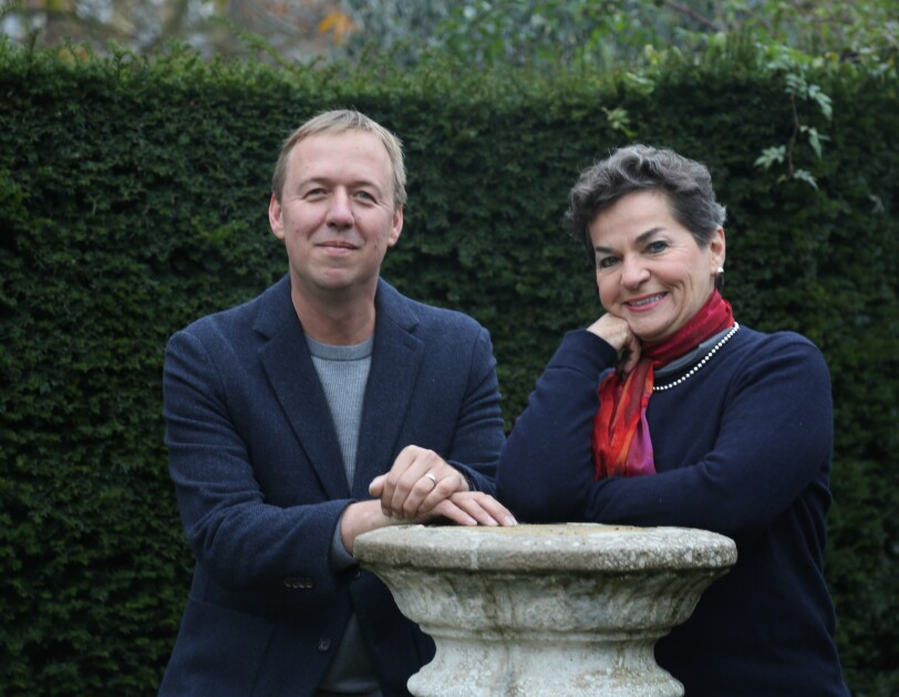 Christiana Figueres standing in a garden with her co-author, Tom Rivett-Carnac, they are leaning on a stone feature.