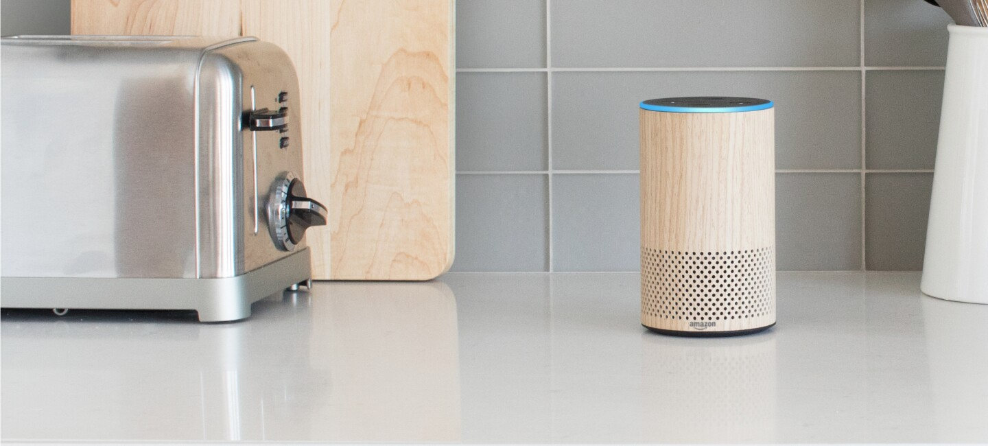 An oak Echo device sits on a kitchen counter. To the left, a stainless toaster and cutting board.