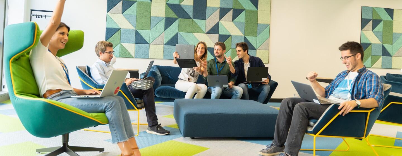 Parte del equipo que prepara el Prime Day se encuentra en una sala de las oficinas corporativas viendo cómo evoluciona el día. Tres de ellos están sentados en el sofá y tres más en sillones. Todos ellos tienen los ordenadores sobre las piernas. Los colores de las paredes y del suelo son amarillos y verdes y azules.