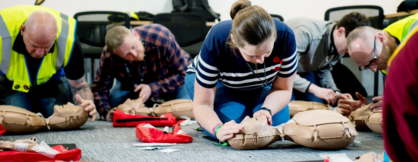 Team of Amazon employees participating in a CPR training course with the British Heart Foundation. They are all using CPR dummies to learn the correct techniques.