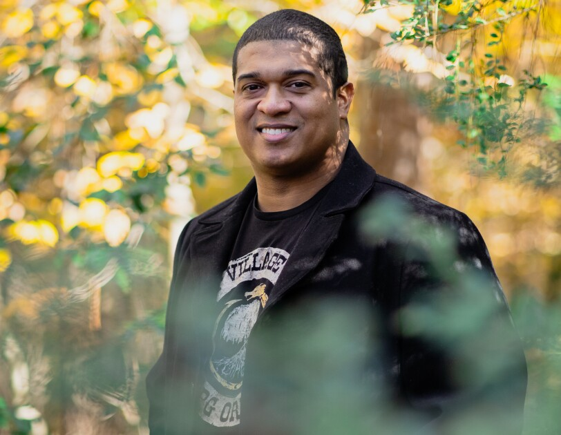A man wearing a blazer and a T-shirt is photographed amidst foliage. Shown from the waist up, he has a short hair and smiles while looking directly into the camera.