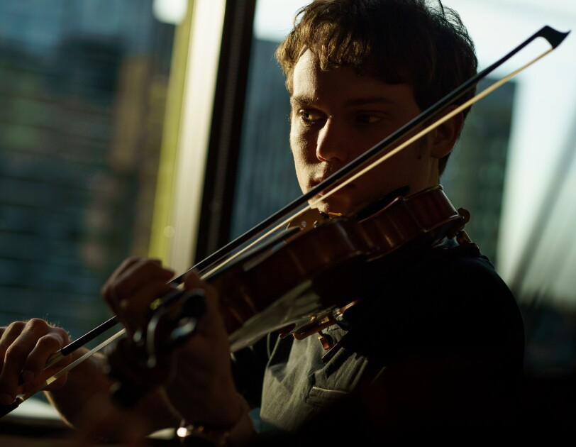 A man plays a violin next to a bank of windows. Tall buildings are in the background.