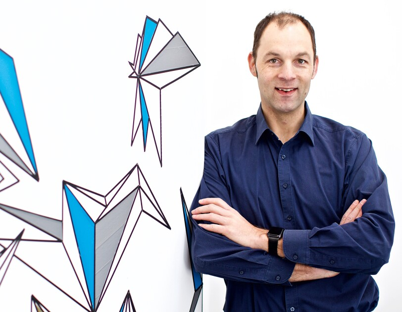Ralf Herbrich, co-head of Amazon's Core Artificial Intelligence (AI) group. He wears a navy button down and leans against a white background with blue and gray illustrations.