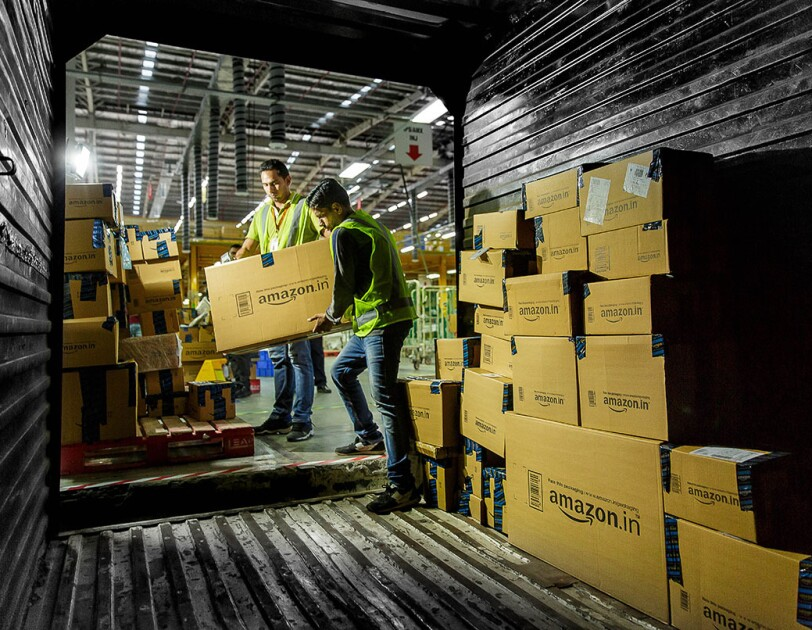 Two Amazon associates are working to load a truck with packages to be delivered to customers. They are both holding onto a large box as one of the associates steps into the trailer of a truck. Within the truck, there is a wall of packages, prepared for delivery.