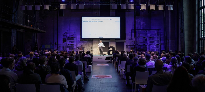 Ralf Kleber steht auf der Bühne der Amazon Academy 2017. Die Location ist voll mit Publikum und in der Mitte des Bilde sieht man den Mittelgang.