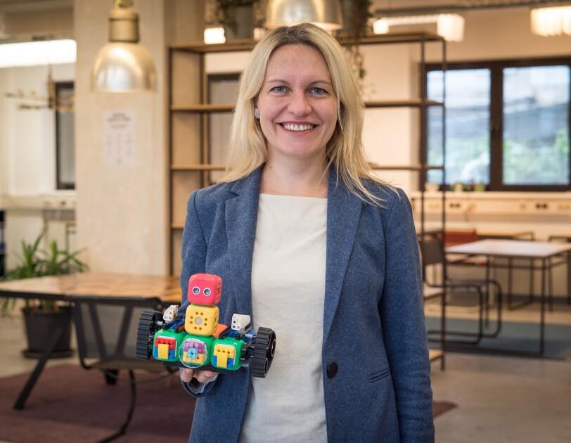 Eine Frau mit langen blonden Haaren hält ein Kinderspielzeug in einer Hand und lächelt in die Kamera.