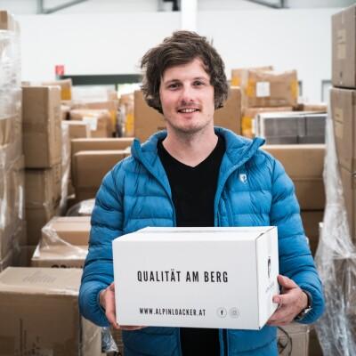 Ein dunkelhaariger Mann mit einer hellblauen Jacke lächelt in die Kamera. Er trägt einen weißen Karton mit der Aufschrift Qualität am Berg.