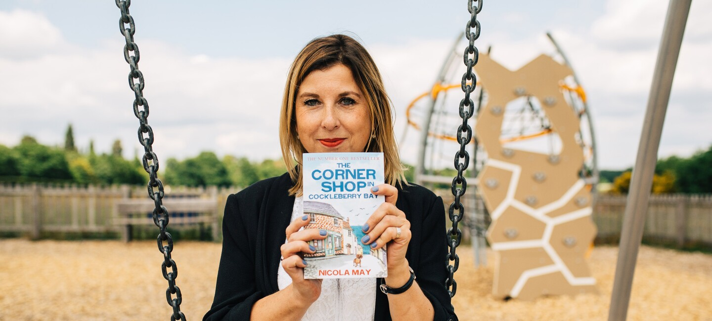 KDP author Nicola May sitting on a swing, holding here newest novel: The Corner Shop in Cockleberry Bay