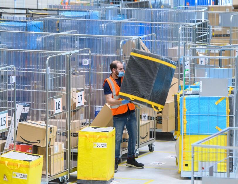 Mitarbeiter im Verteilzentrum umgeben von Paketen und Versandtaschen.