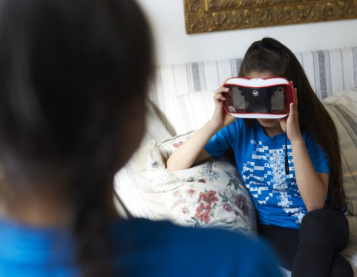 Bambina seduta su un divano indossa i visori Curiscope e indossa una t-shirt Curiscope.