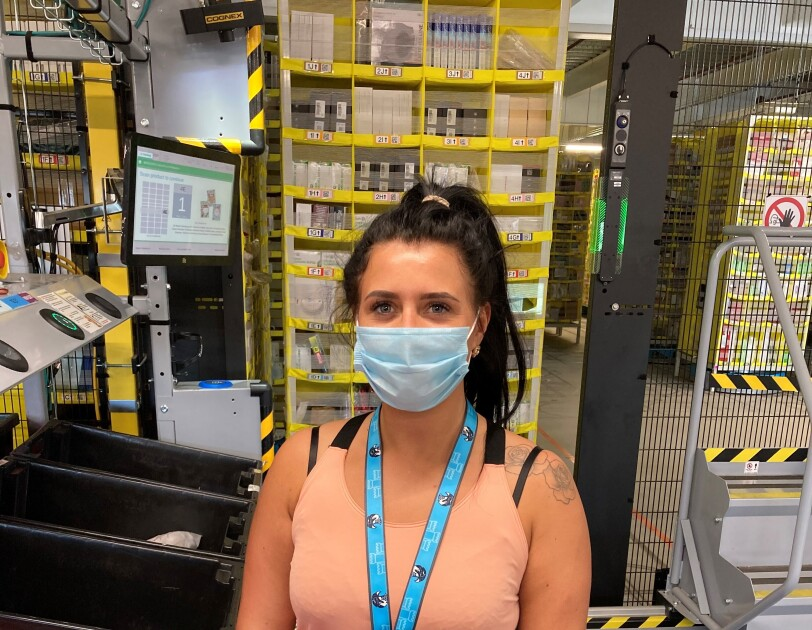 Danelle Ferguson, associate at Amazon's fulfilment centre in Durham, standing at her workstation, wearing a facemask.