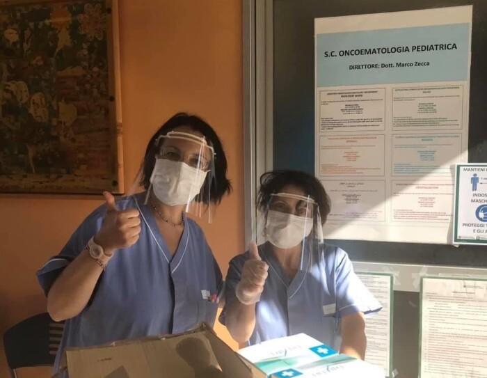 Due donne indossano una mascherina di plastica sugli occhi e una mascherina chirurgica sul volto. Guardano in camera e fanno segno 'OK' con il pollice verso l'alto. Di fronte a loro, alcune scatole di viveri.
