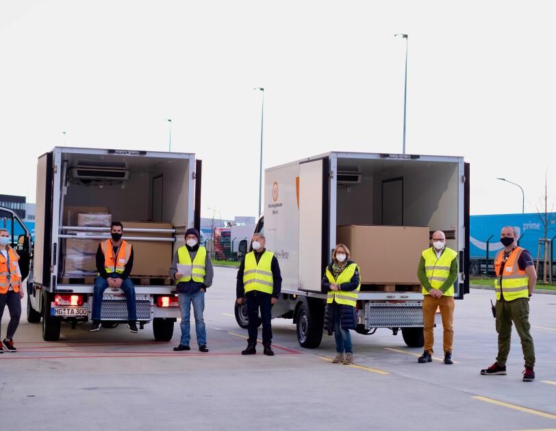Mitarbeiter von Amazon und der Tafel vor 2 Tafel-Lieferwagen.