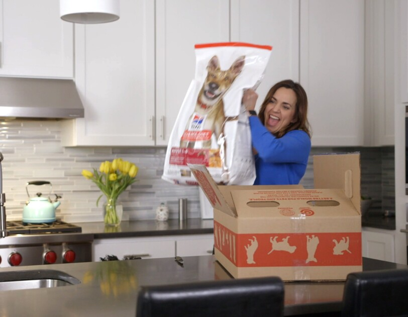 A woman lifts a bag of dog food from a cardboard box. She is standing in a kitchen.
