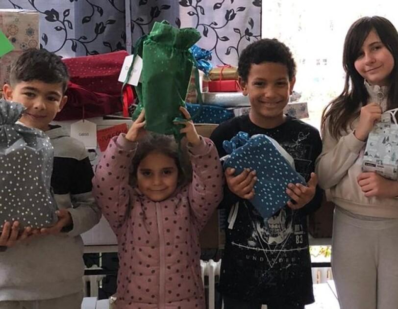 Kinder zeigen stolz ihre Geschenke. Ein kleines Mädchen hält ein grünes Präsent hoch über seinen Kopf.