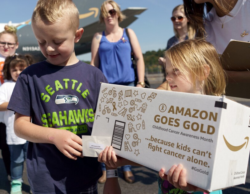 A little girl holds an Amazon Goes Gold box. Next to her is a little boy. Behind them are four women and another girl, and the Amazon Prime Air plane wrapped with #GoGold messaging.