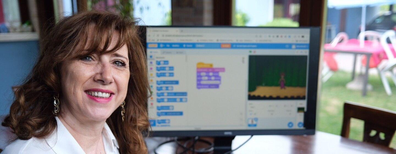 Mezzo busto di una donna in camicia bianca. Siede di fronte a un computer e a un tablet posati su una scrivania.