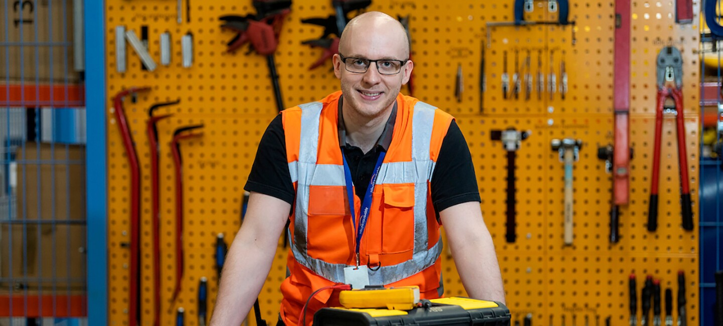 Luke Vials standing with his toolbox at his workbench wearing an orange high-viz vest.