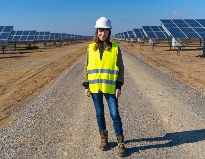 Denise Hugo, jefa de proyectos de Energías Renovables de Amazon. Ella está en medio de la foto, en un camino de tierra y entre dos líneas de placas solartes. Va vestida con unas botas marrones, unos vaqueros, casco blanco y chaleco amarillo.