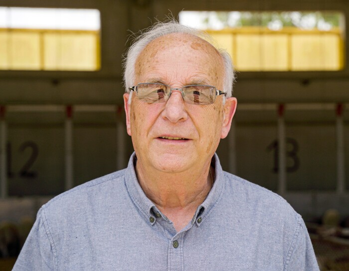 Primer plano de Jaume Farràs. Está en el establos y detrás tiene ovejas. Ell lleva una camisa azul claro y una gafas oscuras. Tiene unos 80 años y el pelo blanco.