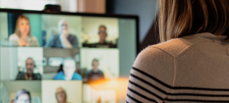 Eine Frau sitzt mit dem Rücken zur Kamera an einem Schreibtisch. Im Bildschirm des Laptops auf dem Schreibtisch läuft ein Videocall.