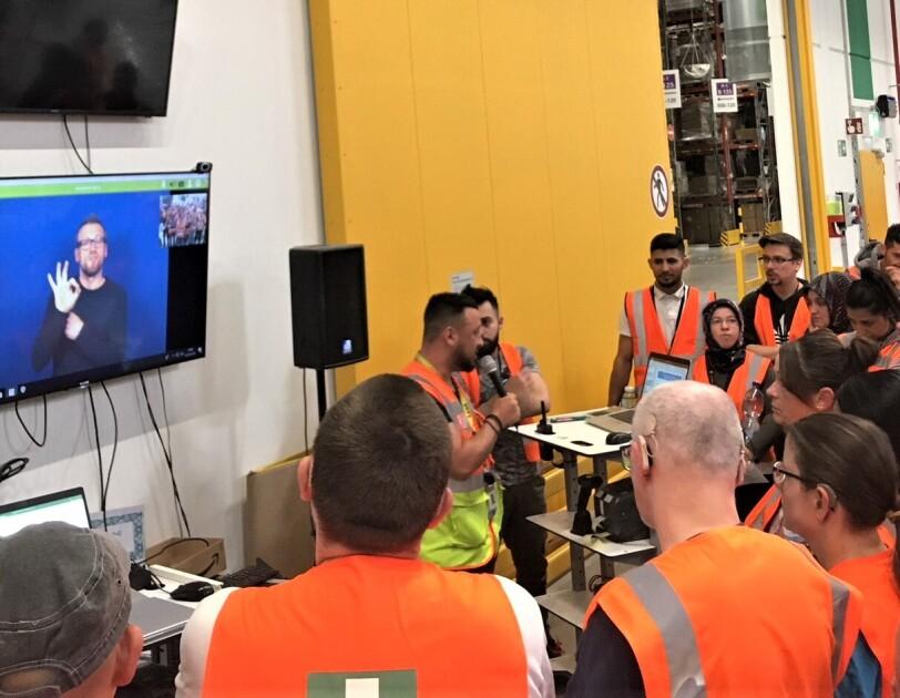 Das Bild zeigt Mitarbeiter bei Start-Meeting: Ein Manager spricht in eine Mikrofon, an der Wand hängt ein Screen, auf dem gerade eine Videokonferenz mit einem Gebärdendolmetscher läuft.