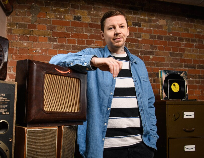 Rapper and mental health advocate, Professor Green, standing next to some vintage speakers.