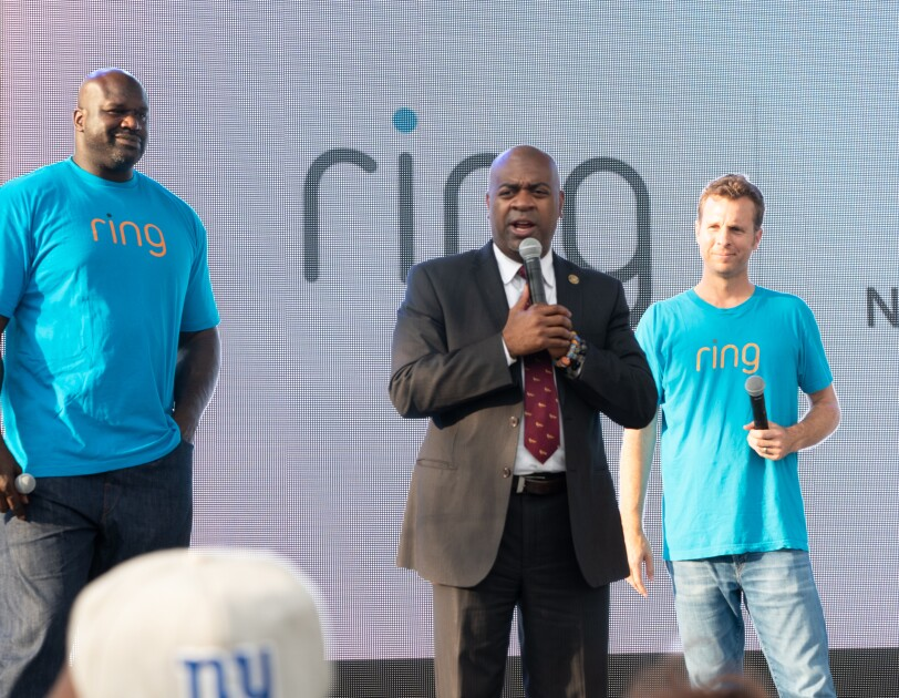 Ring team members in blue t-shirts that have Ring on them with residents of Newark, NJ. Mayor Ras Baraka is wearing a dark suit.