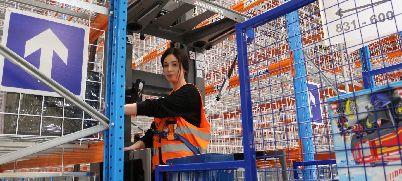 Ein Logistikmitarbeiterin fährt einen Vertikal-Kommissionieren. Im Hintergrund sieht man die neuen Hochregale.