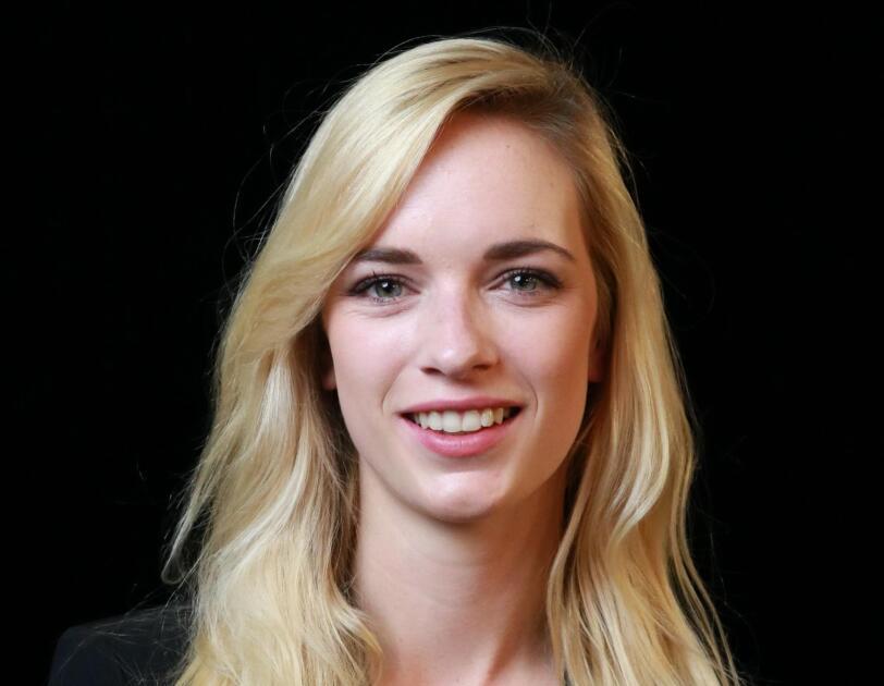Eine Frau mit blonden langen Haaren und einem weißen T-shirt mit schwarzem Blaser schaut in die Kamera und lächelt.