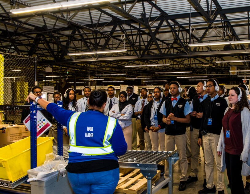 High school students wearing school uniforms and headphones stand in a group within an Amazon fulfillment center. They face an Amazon tour leader as she leads them through the facility.