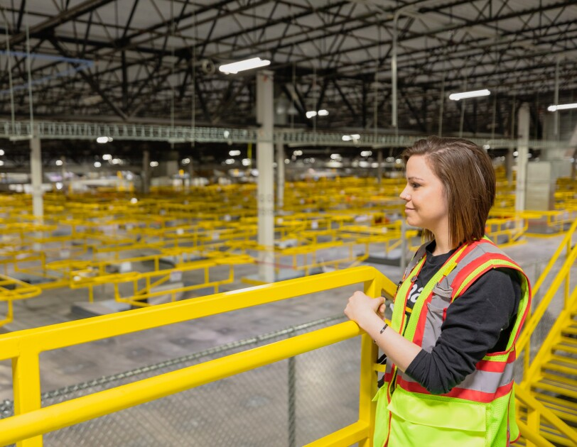 A woman in a safety vest looks out at a large warehouse space.