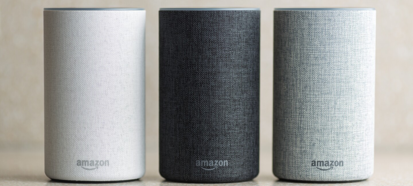 A trio of Amazon Echo devices in white, black, and grey.