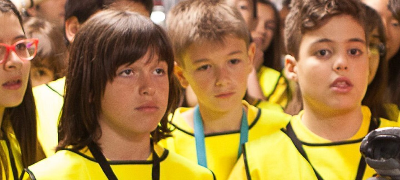 Seis estudiantes de primaria, en primer plano, con sus chalecos amarillos escuchan atentamente las explicaciones de su guía durante el tour por el centro logístico.