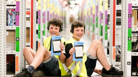 Zwei gleich aussehnde Jungen sitzen Rücken an Rücken in einem Regalgang eines Logistikzentrums. Sie tragen gelbe Sicherheitswesen und halten je einen Kindle in den Händen.