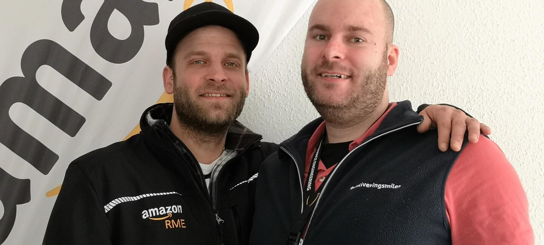 ZWei Männer in schwarzen Jacken sind im Brustprofil zu sehen: Sie umarmen sich. Beide sind bärtig. Der linke Mann trägt eine Base-Cap, der rechte ist barhäuptig.
