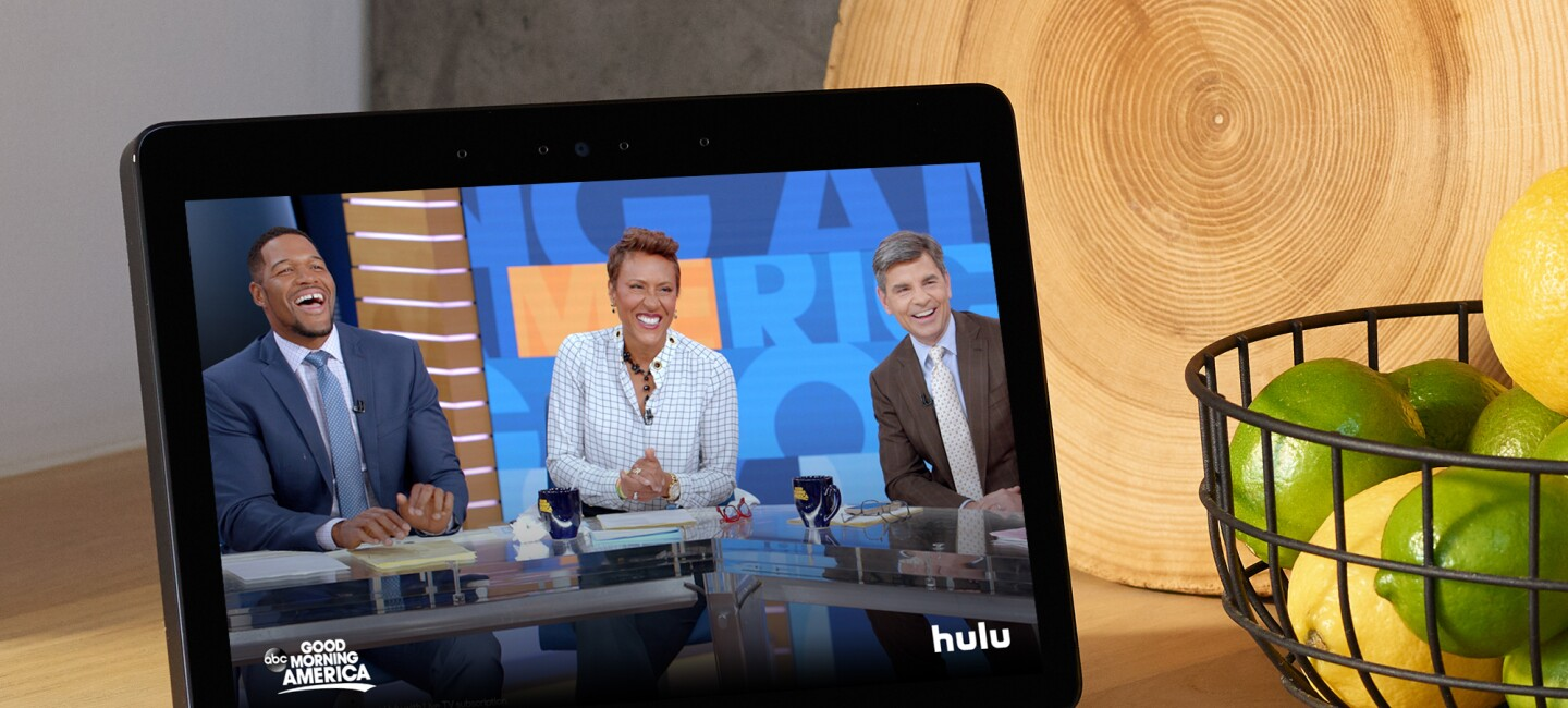 An Echo Show device on a kitchen counter, with Good Morning America displayed on the screen. To the right of the device is a cutting board made of a slice of wood, and a metal basket filled with lemons and limes.